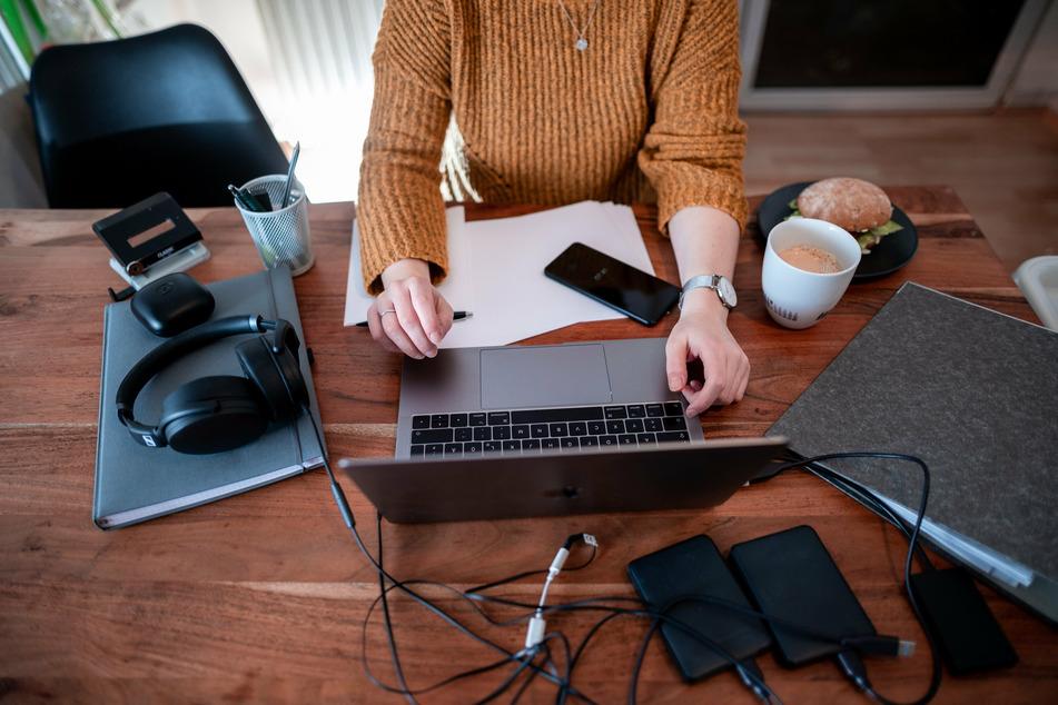 Eine Frau sitzt mit einem Laptop an einem Tisch im Homeoffice.