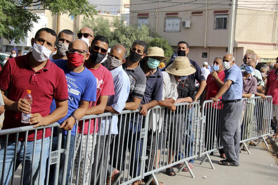 Einwohner warten vor der Assad-Iben-El-Fourat-Schule, um sich während einer Impfaktion mit dem Corona-Impfstoff Vaxzevria impfen zu lassen. Um die katastrophale Corona-Lage in Tunesien in den Griff zu bekommen, hat eine Impfaktion für bis zu eine Million Bürger im Land begonnen.
