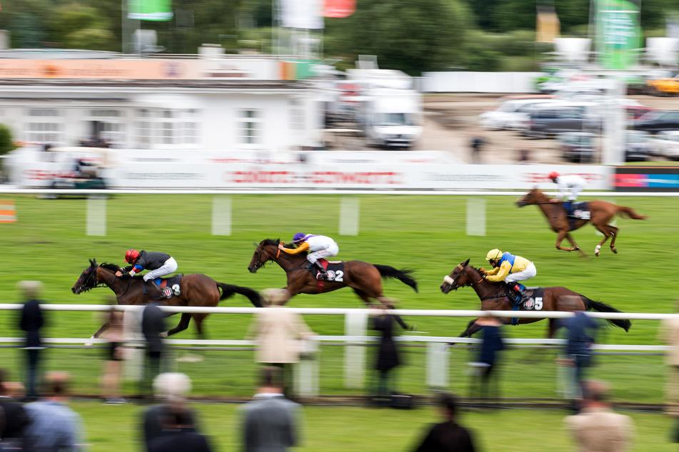 Jockeys galoppieren auf ihren Pferden über die Rennbahn beim 151. Galopp-Derby.