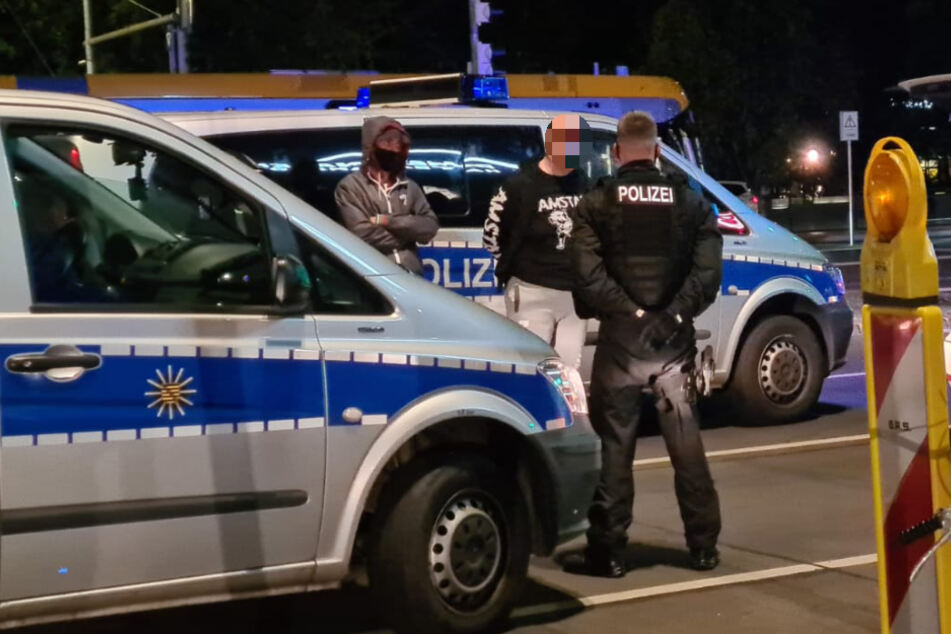 Beamte bewachen einen der Männer, die die Dealerin begleitet hatten - und bei dem Einsatz ebenfalls festgenommen wurden.