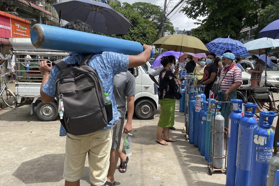Menschen mit ihren Sauerstoffflaschen vor einer Nachfüllstation in Yangon, einer Stadt in Myanmar.