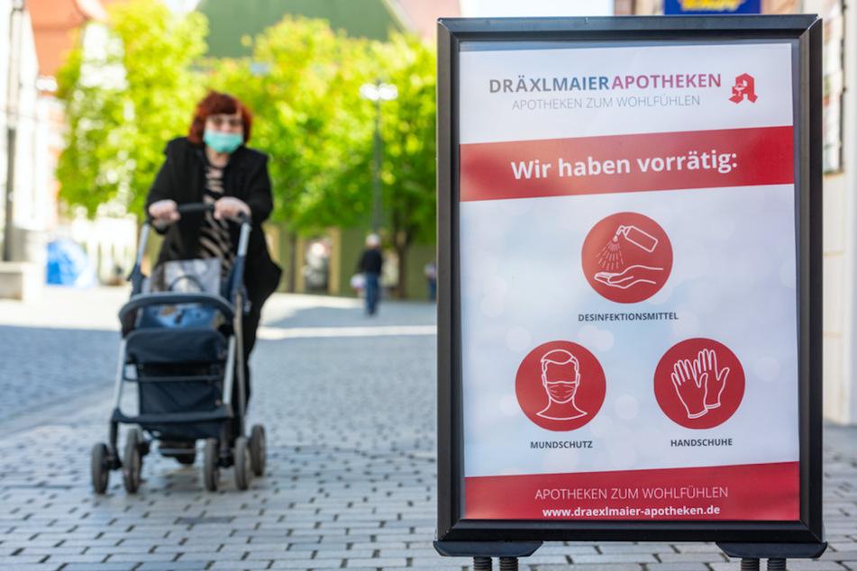 """""""Wir haben vorrätig: Desinfektionsmittel, Mundschutz, Handschuhe"""" steht auf einem Schild vor einer Apotheke in Straubing."""