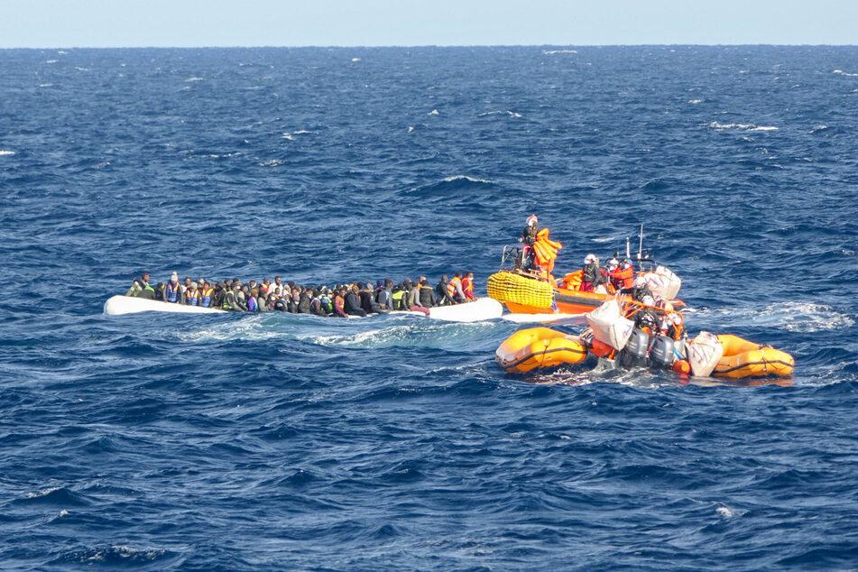 """Rund 120 Geflüchtete aus Libyen sitzen in einem Schlauchboot. Helfer des Seenotrettungsschiffs """"Ocean Viking"""" nähern sich mit weiteren Booten."""