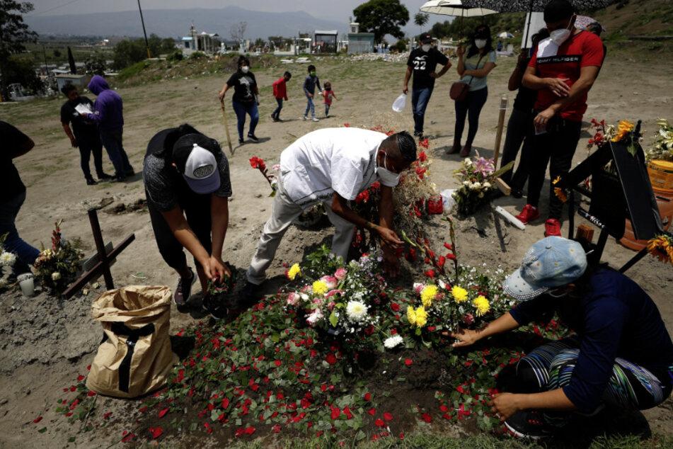 Mexiko, Valle De Chalco: Familienmitglieder bestreuen während der Beerdigung das Grab einer Angehörigen mit Rosenblättern.