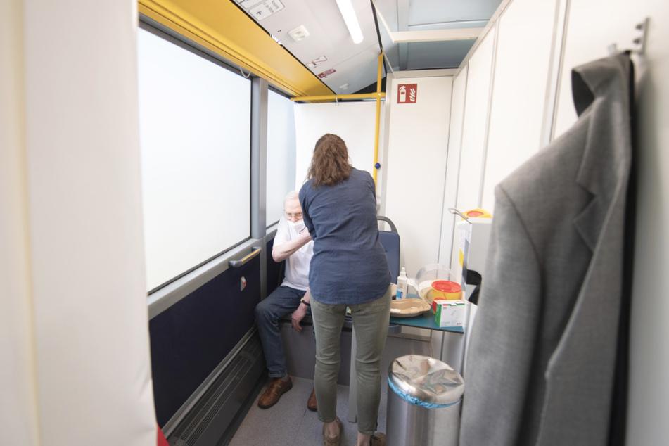 Ein Mann wird in einem Bus geimpft. (Symbolbild)