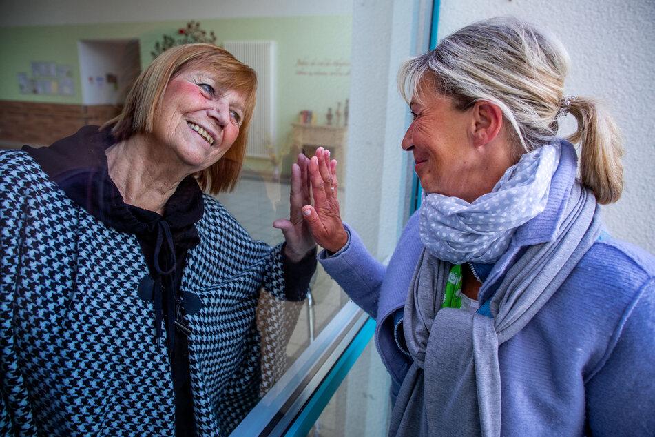 Eine Tochter und ihre Mutter treffen sich im Pflegeheim, sind aber durch eine Scheibe getrennt.