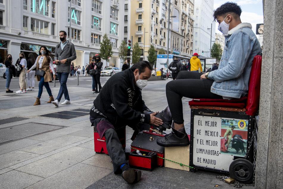 Ein Schuhputzer mit Mund-Nasen-Schutz reinigt die Schuhe eines Kunden in der Avenida Gran Via.