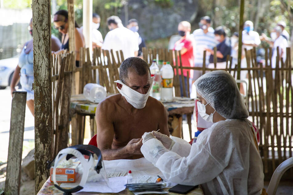 Ein Mann mit Mundschutz und nacktem Oberkörper unterzieht sich einem Covid-19-Schnelltest am Stadtrand von Rio De Janeiro.