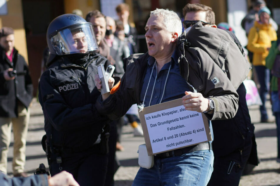 """Ein Demonstrationsteilnehmer wird bei einer Demonstration unter dem Motto """"Grundrechte verteidigen - Sage NEIN zur Diktatur!"""" auf dem Rosa-Luxemburg-Platz von Polizisten abgeführt."""