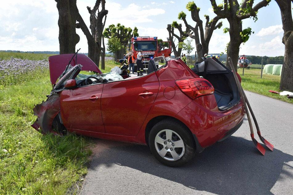 Der Feuerwehrwagen steht vor dem demolierten Wagen. Im Hintergrund (rechts) ist der Rettungshubschrauber zu sehen.