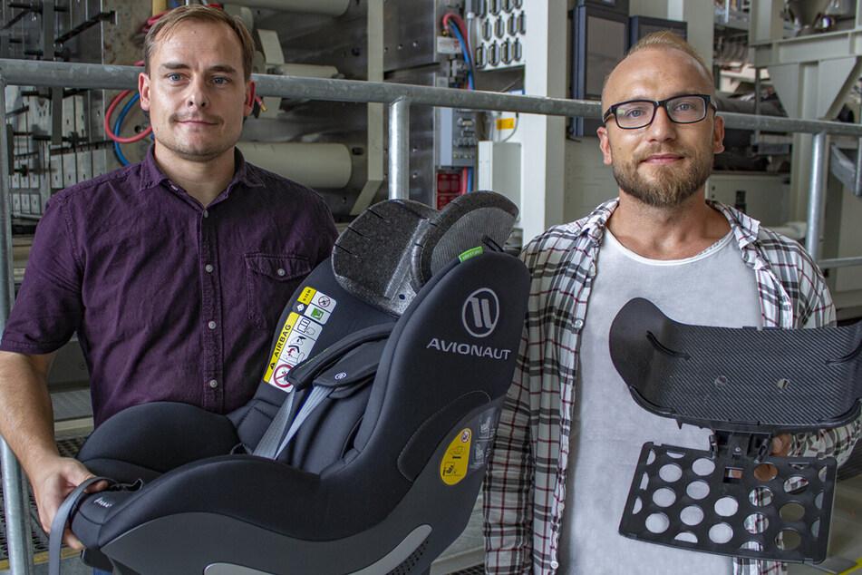 Die TU-Forscher Norbert Schramm (37, l.) und Tomasz Osiecki zeigen einen Kindersitz mit eingebauter Kopfstütze sowie die Organoblech-Preform mit Trägerplatte.