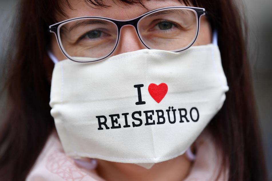 """""""I love Reisebüro"""" ist auf dem Nasen-Mundschutz einer Frau zu lesen, während Thüringer Vertreter von Reisebusunternehmen, Reisebüros und Reiseveranstalter auf dem Domplatz demonstrieren, um auf die schwierige Lage durch das Berufsverbot seit der Corona-Pandemie aufmerksam zu machen."""