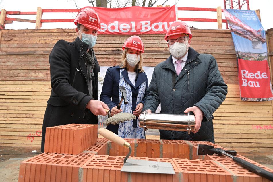 Oberbürgermeister Sven Schulze (49, SPD, v.r.) und die Geschäftsführer der Kommunalbau Chemnitz, Simone Kalew (58) sowie Rocco Brüsch (46), beim Einbringen der Zeitkapsel.
