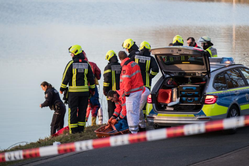 Einsatzkräfte der Polizei und Feuerwehr stehen am Ufer. (Symbolbild)