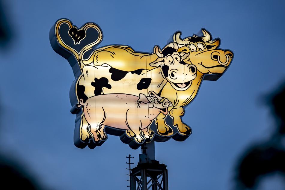 Tiere strahlen als Leuchtreklame am frühen Morgen auf einem Gebäude des Fleischwerks Tönnies. Rund vier Wochen nach dem Corona-Ausbruch bei Deutschlands größtem Fleischbetrieb Tönnies in Rheda-Wiedenbrück darf das Unternehmen an seinem Hauptstandort wieder schlachten.