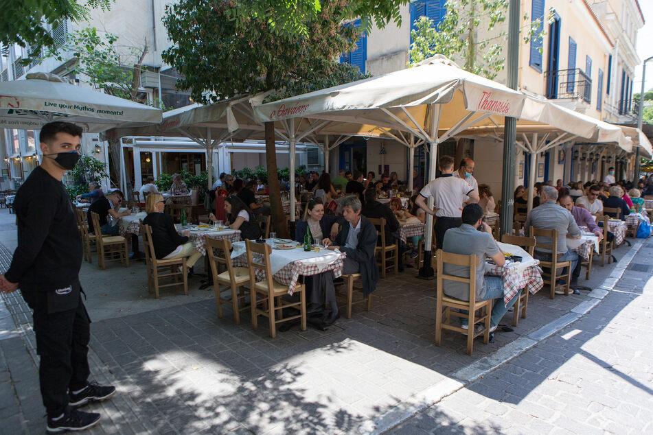 Menschen sitzen an Tischen im Außenbereich eines Restaurants am Monastiraki-Platz. Athen hat angekündigt, den Tourismus aus dem Ausland neu starten zu wollen.