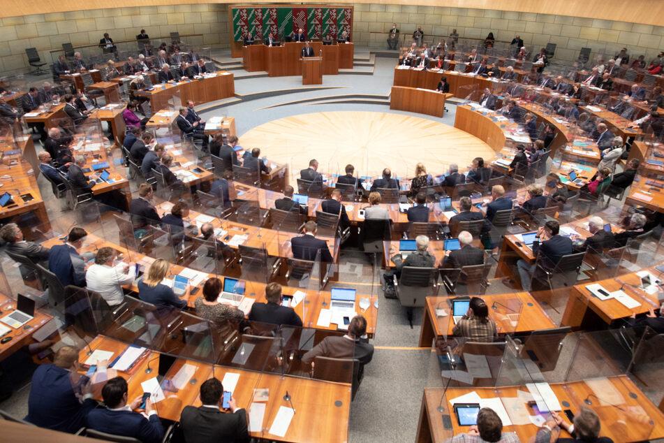 Armin Laschet (CDU, hinten M), Ministerpräsident von Nordrhein-Westfalen, spricht im Landtag. Wegen der Corona-Pandemie kommt der nordrhein-westfälische Landtag zu einer Sondersitzung zusammen.