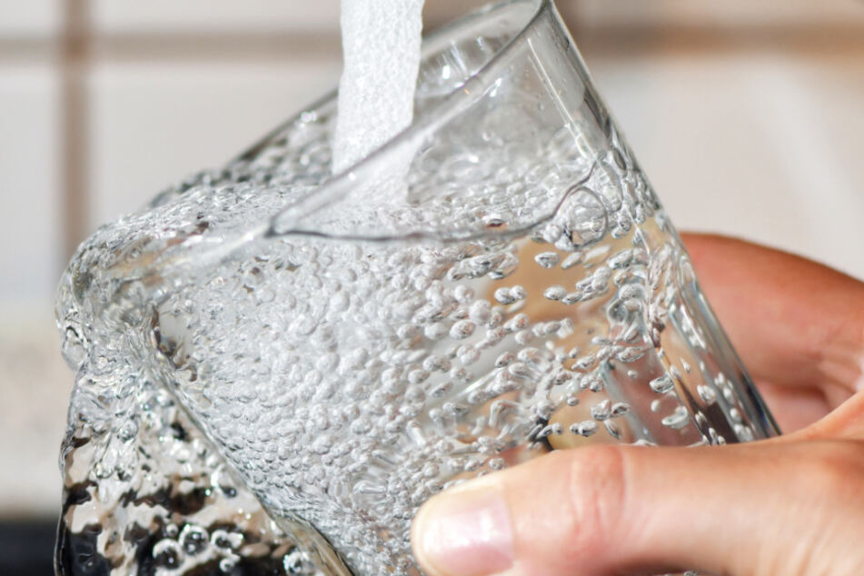 Ein Trinkglas wird an einem Wasserhahn mit Leitungswasser befüllt.