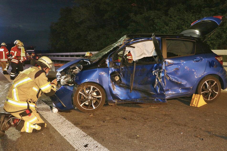 Ein Feuerwehrmann untersucht den Motorraum des Unfallwagens. Ein Mann krachte zuvor in die Leitplanke.