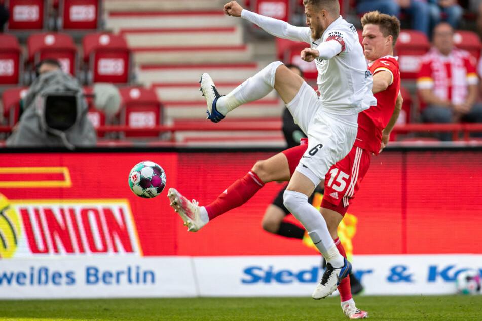 Jeffrey Gouweleeuw (29, l) von FC Augsburg kämpft gegen Berlins Marius Bülter (27) um den Ball.