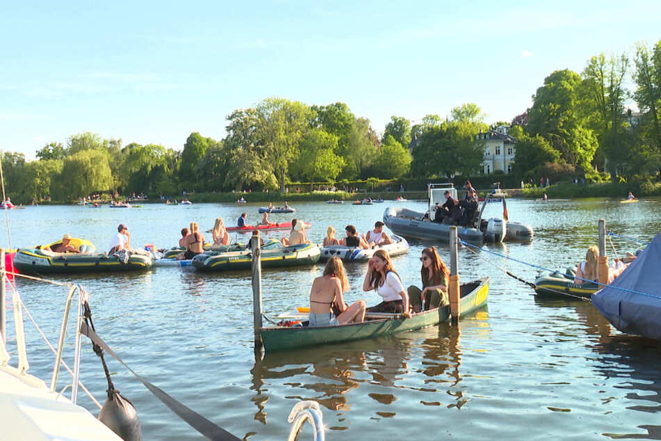 Polizisten ermahnen die jungen Menschen auf dem Wasser, sich an die Kontaktbeschränkungen zu halten.