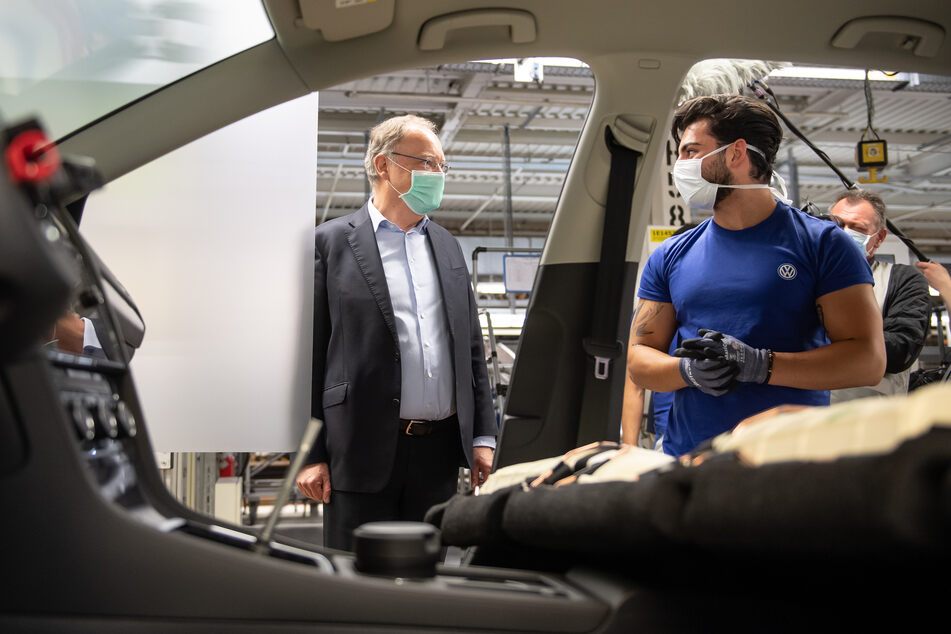Stephan Weil (SPD, l), Ministerpräsident von Niedersachsen, und ein Mitarbeiter stehen mit einem Mund- und Nasenschutz in der Produktion von Volkswagen in Wolfsburg.