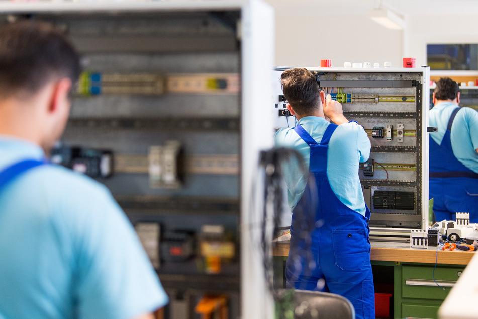 Drei junge Flüchtlinge arbeiten im Ausbildungszentrum der Siemens Professional Education in Sachsen. Die Pandemie erschwert die Entwicklung für geflüchtete Menschen, die in Deutschland Fuß fassen möchten.