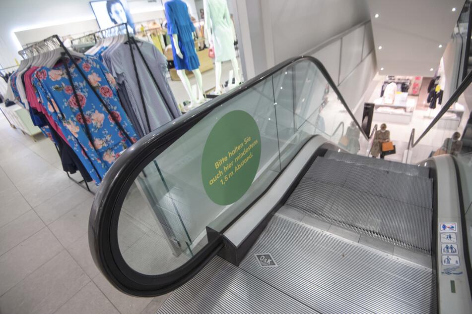 Ein Aufkleber auf einer Rolltreppe im Kaufhaus Breuninger weist auf den Mindestabstand hin.