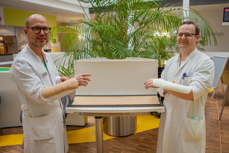 Prof. Martin Lacher (links), Direktor der Klinik und Poliklinik für Kinderchirurgie, mit einem Holzgips, Studienleiter Dr. Ilya Martynow mit einem herkömmlichen Plastikgips.