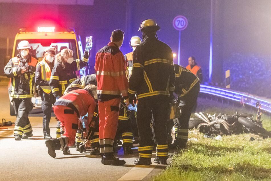Rettungskräfte versorgen den verletzten Motorradfahrer am Unfallort.