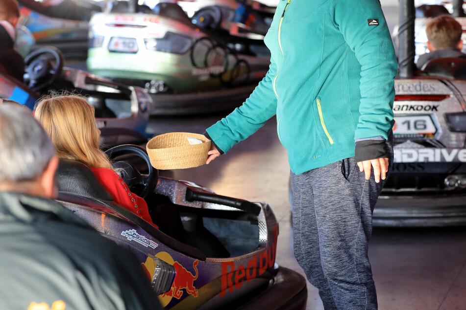 """Freiwillige sammeln für die Kollekte beim Gottesdienst von Circus- und Schaustellerpfarrer Conrad Herold im Autoscooter auf dem Messeplatz """"Max Wille""""."""