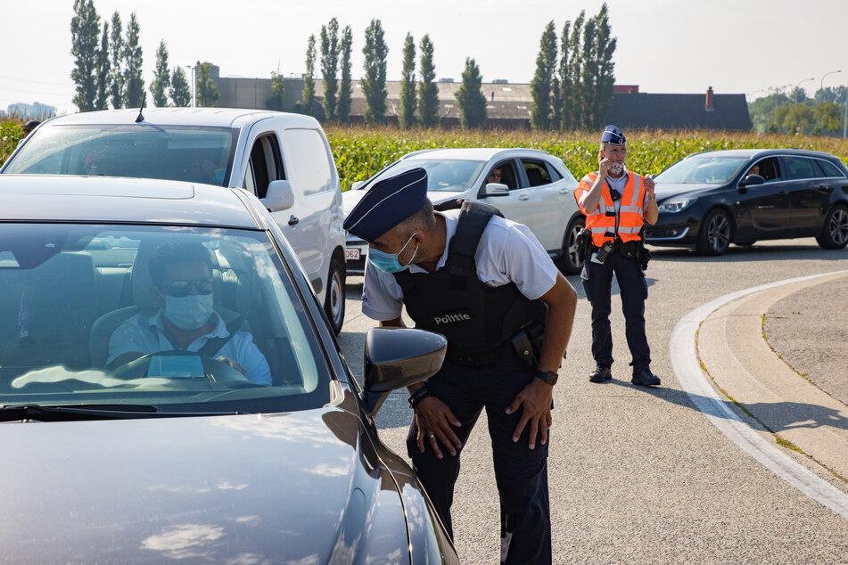 Belgien, Blankenberge: Polizeibeamte kontrollieren Autofahrer.