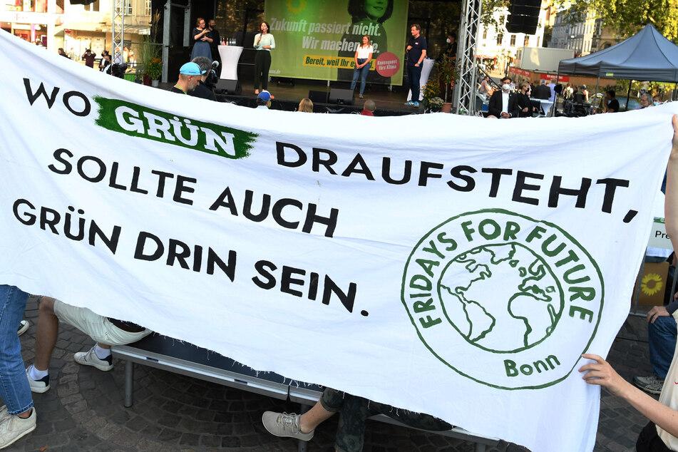 Aktivistinnen von Fridays for Future protestieren während der Rede von Annalena Baerbock (hinten) bei deren Wahlkampfauftritt auf dem Münsterplatz.