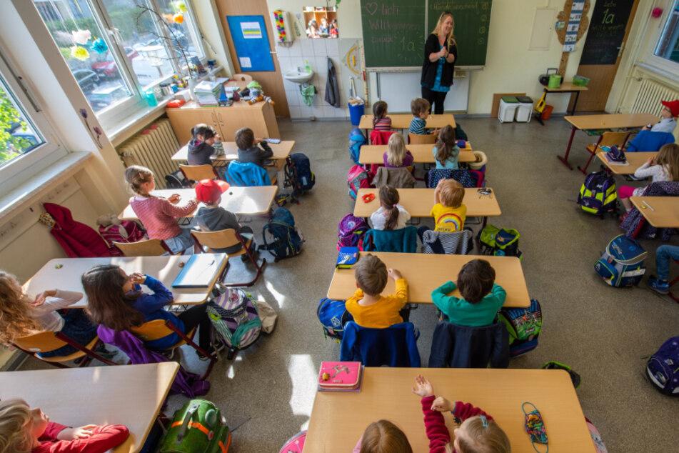 Schüler einer Grundschulklasse sitzen auf ihren Plätzen.