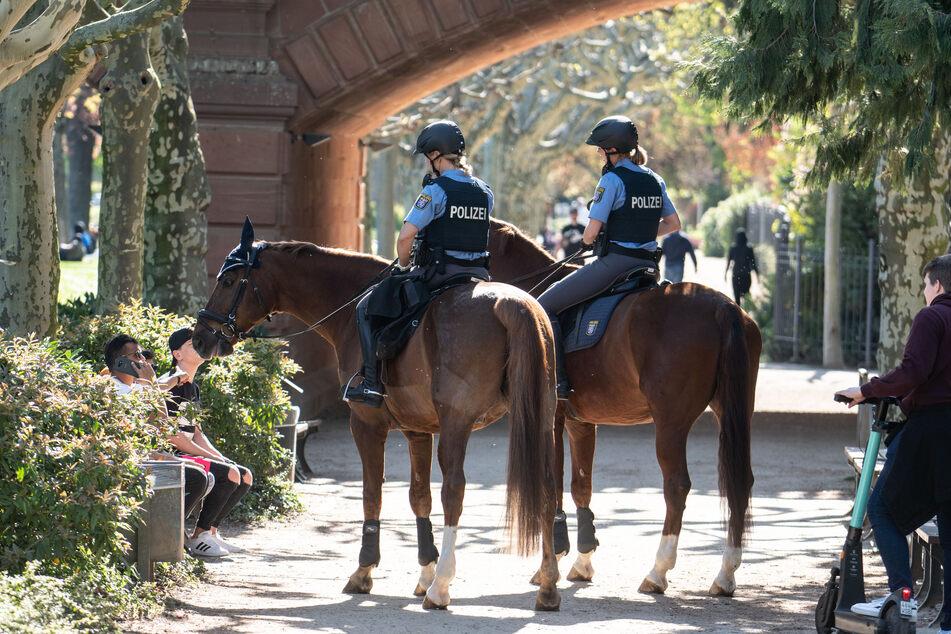 Zwei Polizistinnen reden mit drei jungen Männern (l.), die zusammen auf einer Bank sitzen, während sie auf ihren Pferden am nördlichen Mainufer entlang reiten, um die die Einhaltung des Kontaktverbotes zu kontrollieren, das wegen der Corona-Pandemie immer noch besteht.