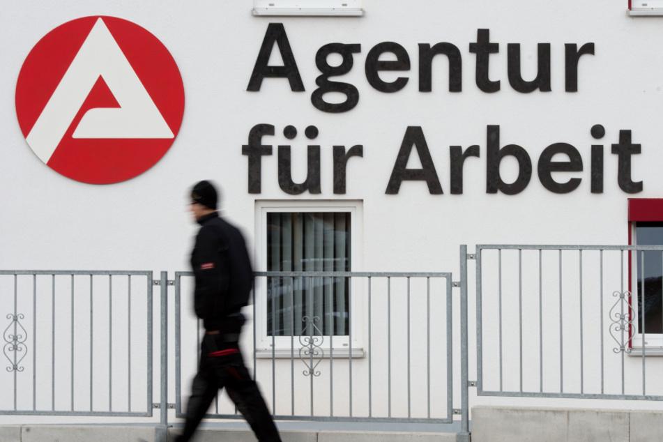 Ein Mann geht an dem Logo der Agentur für Arbeit vorbei.