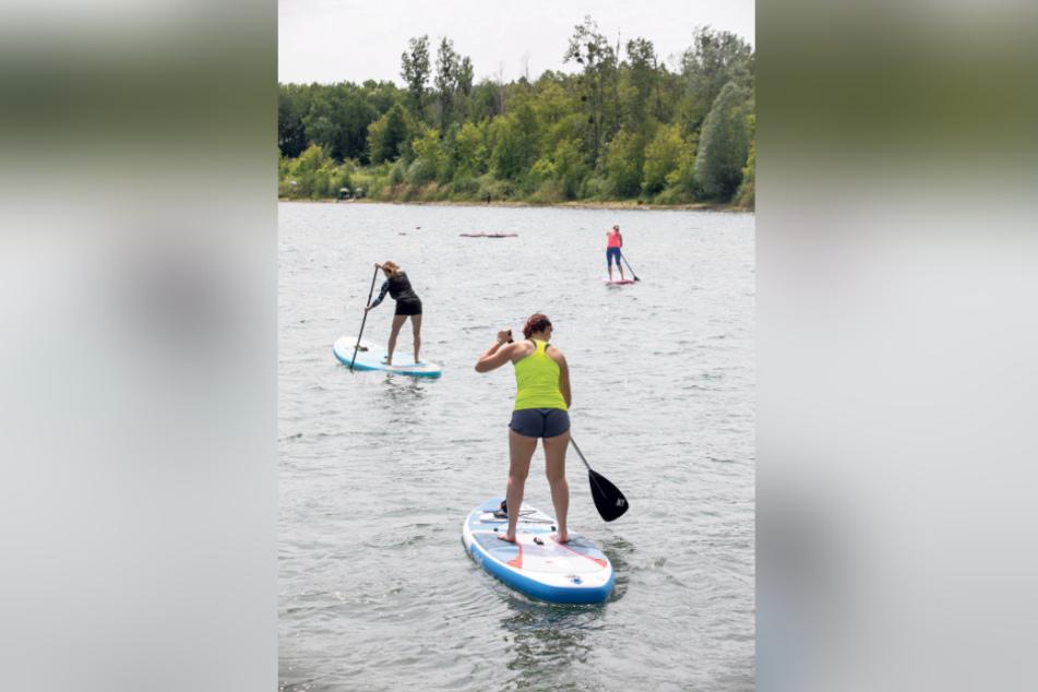 """Auf einem weichem Surfbrett (""""stand up paddle board"""") paddeln die Teilnehmer für die Übungen aufs Wasser."""