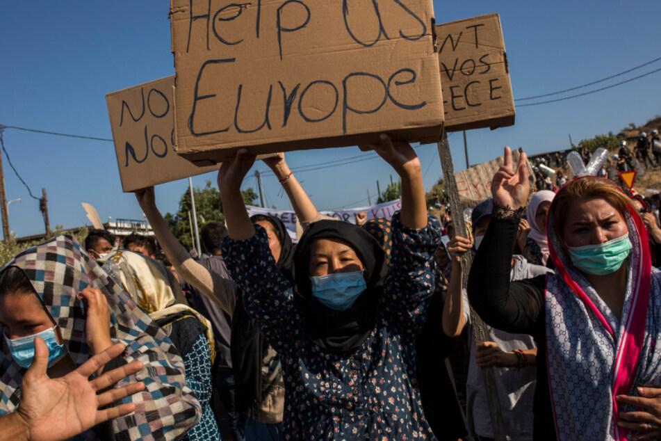 """Eine Frau hält einen Karton mit der Aufschrift """"Hilf uns Europa"""" während eines Protestes nach den Nachrichten über die Schaffung eines neuen provisorischen Flüchtlingslagers auf der Insel Lesbos hoch."""