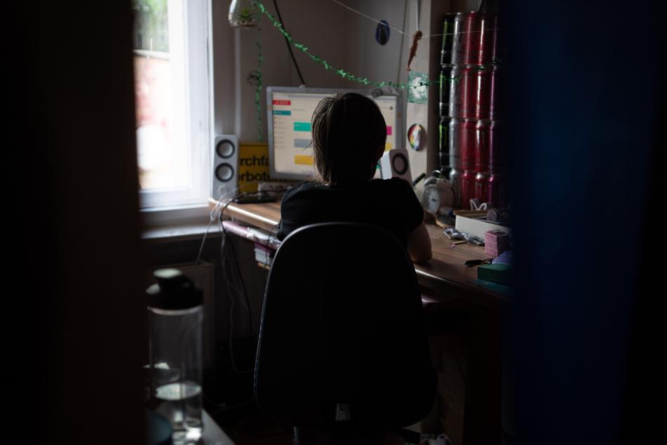 Eine Jugendliche sitzt in einem abgedunkelten Zimmer vor ihrem PC beim Homeschooling.
