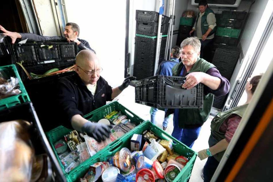 Mitarbeiter der Rostocker Tafel laden Lebensmittel um.
