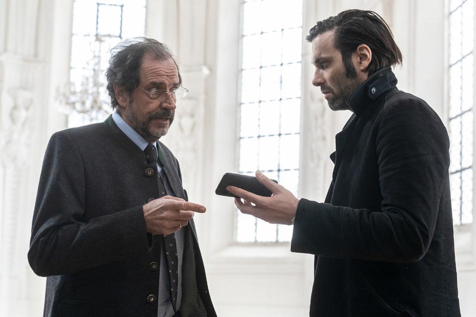 Lukas Laim (Max Simonischek, r.) zeigt Lutz Grindel (Helmfried von Lüttichau, l.) ein Video auf seinem Handy.