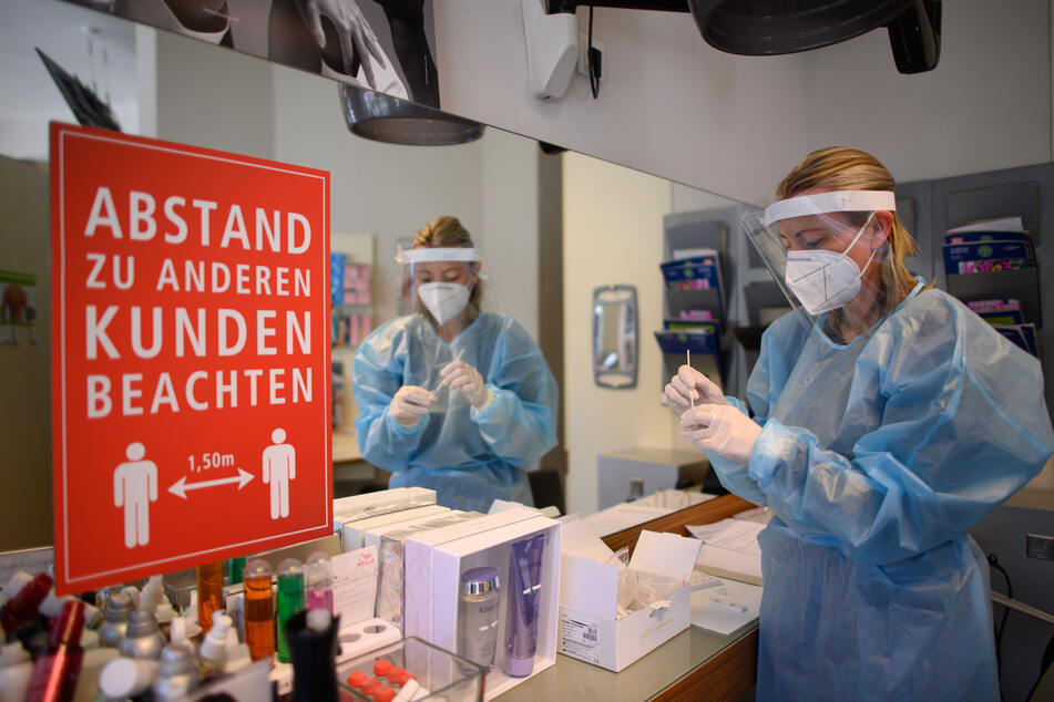 Eine Mitarbeiterin im Dresdner Friseurstudio Holger Knievel wertet einen Antigen-Schnelltest aus.