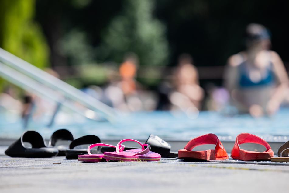 Menschen baden bei strahlendem Sonnenschein und blauem Himmel in einem Schwimmbecken des Kölner Stadionbads.