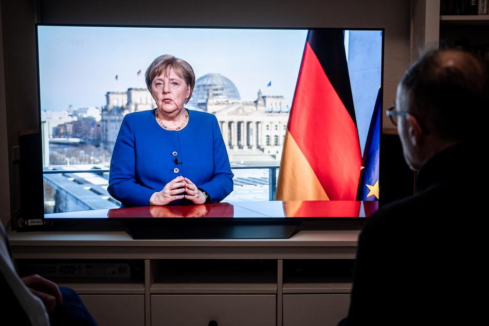 Menschen schauen die TV-Ansprache der Bundeskanzlerin Angela Merkel (66, CDU) in einem Wohnzimmer. Die Bundeskanzlerin redet über die Coronavirus-Pandemie.