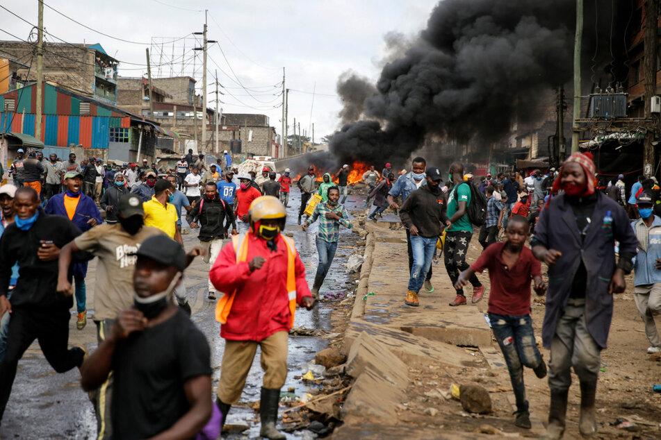 8. Mai 2020, Nairobi: Demonstranten und Bewohner des Kariobangi Slums fliehen vor Polizisten. Hunderte Demonstranten haben eine Autobahn mit brennenden Reifen blockiert, um gegen den von der Regierung in Auftrag gegebenen Abriss von Häusern zu protestieren, in denen mehr als 7000 Menschen leben. So müssen aufgrund der Corona-Ausgangsbeschränkungen viele Menschen auf der Straße schlafen.