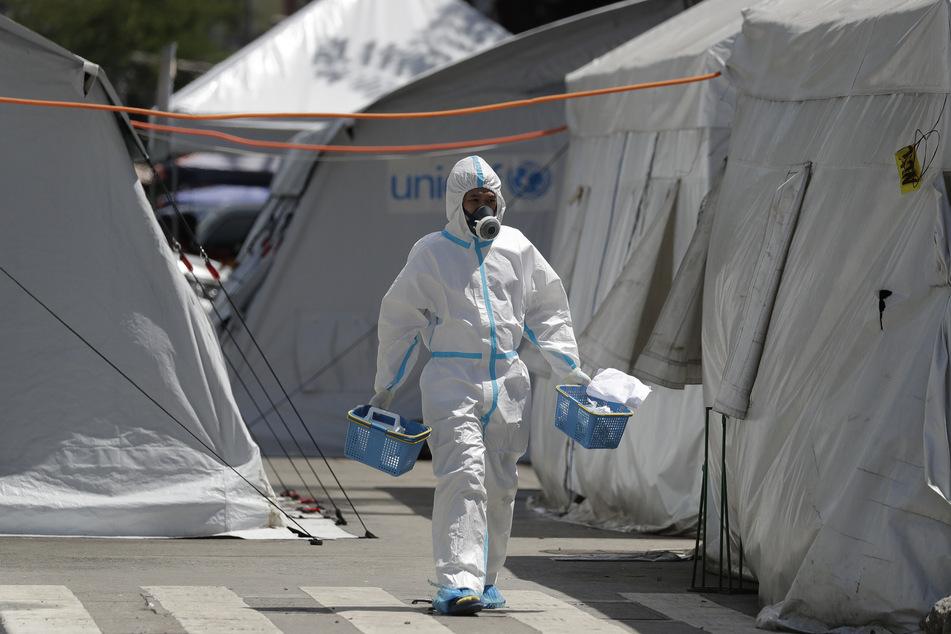 Ein Gesundheitsmitarbeiter in einem Schutzanzug geht auf einem Parkplatz, der zu einer medizinischen Einrichtung umgebaut wurde, zwischen Zelten hindurch.