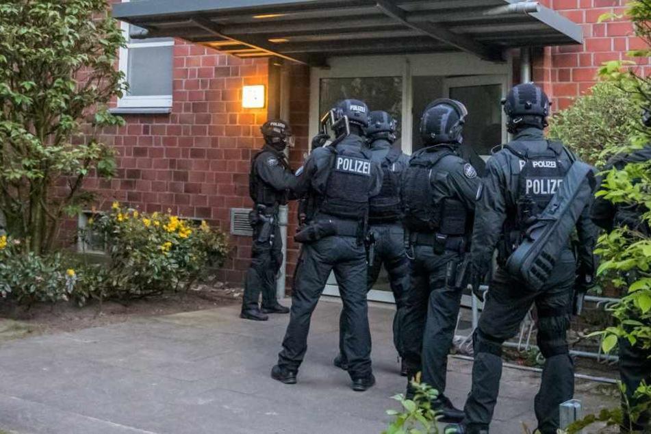 Beamte der Beweissicherungs- und Festnahmeeinheit (BFE) stehen vor dem Hauseingang.