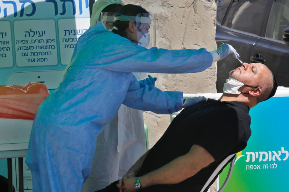 Eine medizinische Mitarbeiterin entnimmt in der zentralisraelischen Stadt Lod einem Mann eine Probe für einen COVID-19-Test.