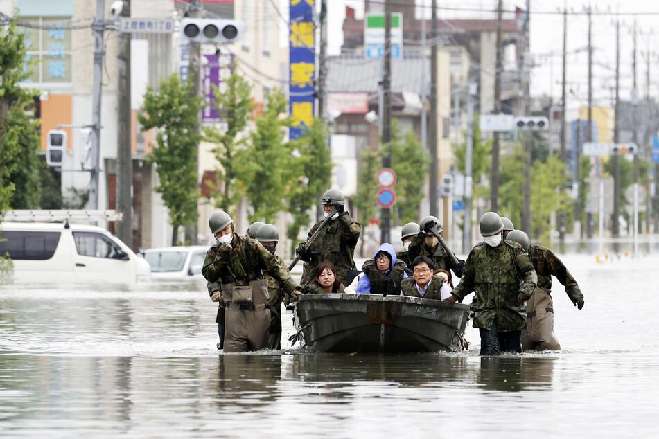 Mitglieder des japanischen Militärs retten Bewohner Omutas mithilfe eines Bootes auf einer überfluteten, von heftigen Regenfällen heimgesuchten Straße.