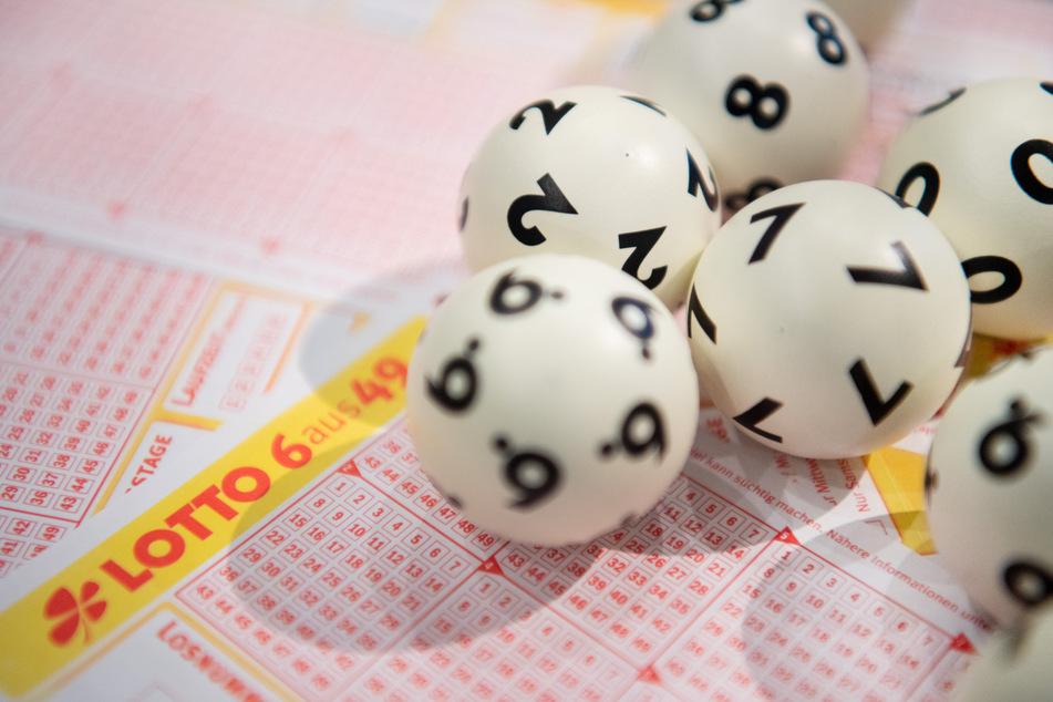 LOTTO-Kugeln liegen auf einem Lottoschein (Symbolbild).